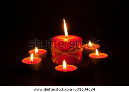 Some red candles at wooden table. Burning in the night.