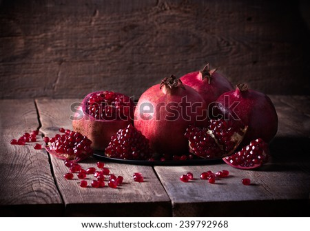 Some red juicy pomegranate on dark rustic wooden table - stock photo