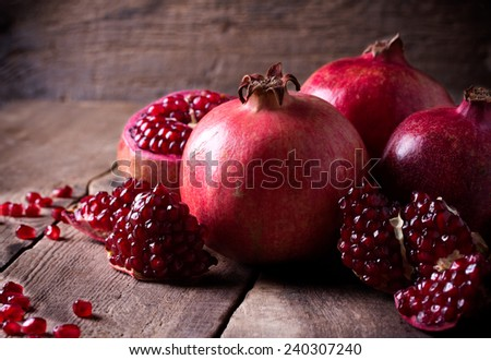 Some red juicy pomegranate, whole and broken, on dark rustic wooden table - stock photo