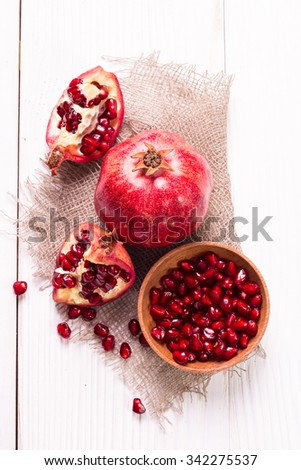 Some red juicy pomegranate, whole and broken, on  rustic wooden table.healthy food.