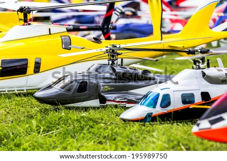 some remote controlled helicopter are placed in a line on the grass - stock photo