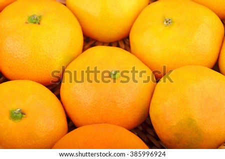 Some ripe mandarin fruit on wickered background - stock photo