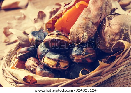 some roasted chestnuts and some roasted sweet potatoes in a wicker basket with autumn leaves, on a rustic wooden table - stock photo