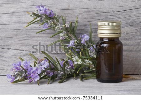 Some rosemary branches and a jar with essential oil. - stock photo