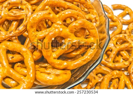 some salted pretzels on a plate closeup on white