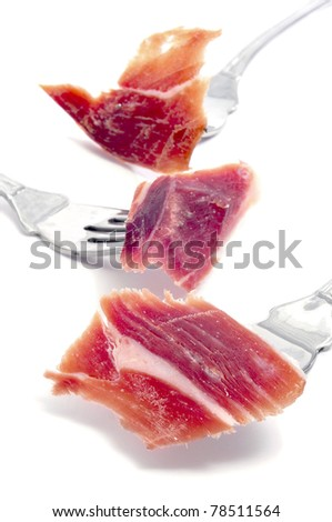 some slices of serrano ham in fork on a white background