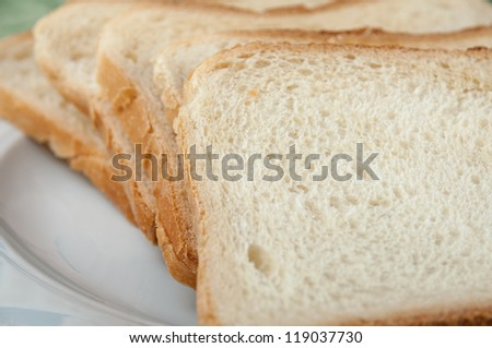 Some slices of toast bread on a white plate - stock photo