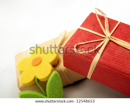 Some small gifts with bows from straw and with artificial flowers - stock photo