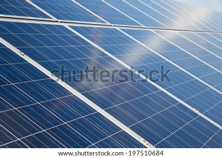 Some solar panels with vague reflection of wind turbine