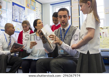 Some students each sit with a teacher practicing and learning to read at the front of the class. - stock photo
