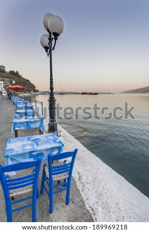 Some tables and chairs that belong to a tavern, in a row, on a jetty of Ikaria island, Greece, port,  during sunset. - stock photo