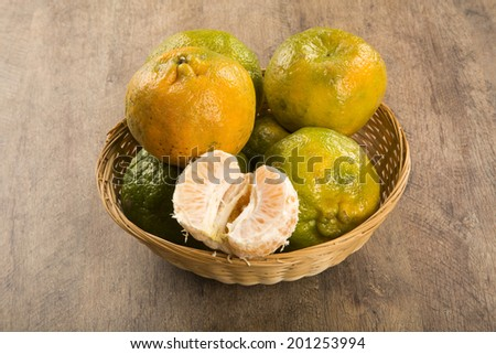 Some tangerines in a basket over a wooden surface