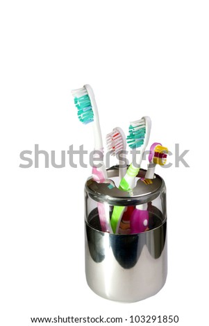 some toothbrushes in a metallic glass isolated in white - stock photo