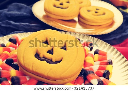some trays with pumpkin-shaped cookies and some different Halloween candies, with a filter effect