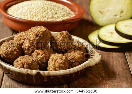 some vegan meatballs in an earthenware plate on a rustic wooden table, with some vegetables in the background - stock photo