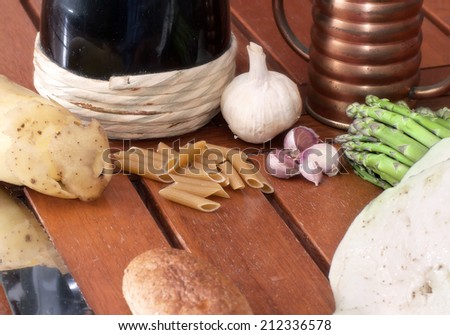 Some vegetables, one knife and a flask of red wine on a wooden table