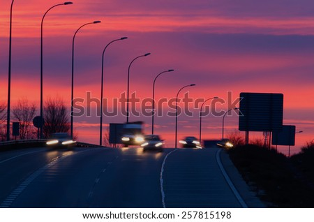 Some vehicles in motion at morning in an spanish road. Night traffic - stock photo