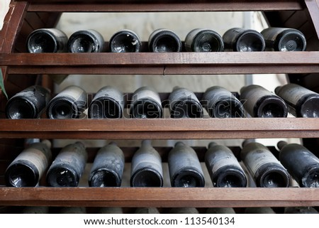 some very old and dusty wine bottles in a wine cellar - stock photo