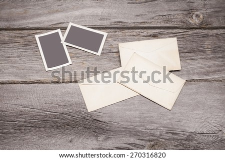 Some vintage photographs and envelopes sit on top of a rustic wooden table top. The frames are blank and can easily be filled with your photographs. - stock photo