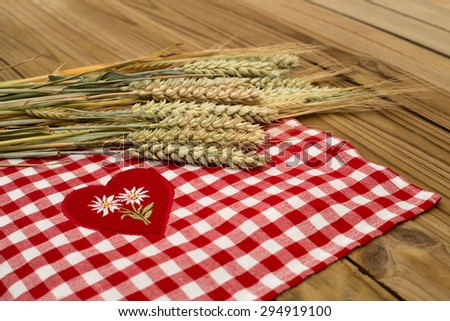 Some wheat, rye, barley ripe cereal ears on a background of red and white checkered tablecloth with a red heart and two embroidered white Edelweiss on rustic wooden table surface - stock photo