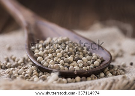 Some white Peppercorns (close-up shot) on wooden background