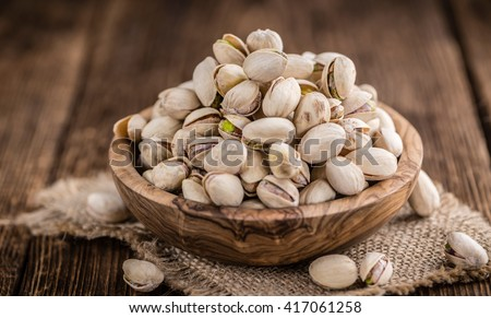 Some whole Pistachios (selective focus; close-up shot) on wooden background