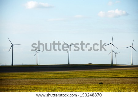 Some wind mills on a meadow, under a cloudy sky