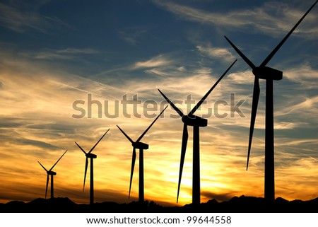 Some wind turbines silhouette in the sunset sky - stock photo