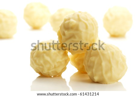 some yellow truffle pralines in front of others on white background - stock photo