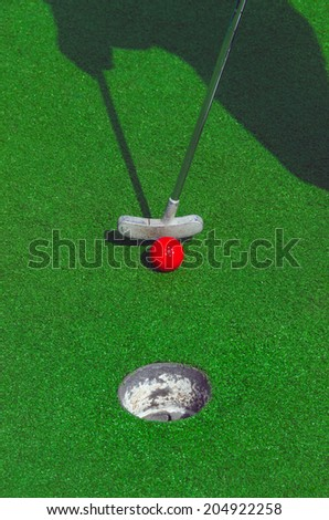 Somebody is playing minigolf with a red ball. Mini golf recreation - stock photo
