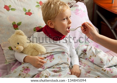Somebody pours spoon liquid syrup of medicine for flu and cold for sick boy. - stock photo