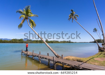 somebody selfie on wood jetty river with bluesky