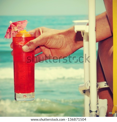 someone chilling out with a cocktail on the beach, with a retro effect - stock photo