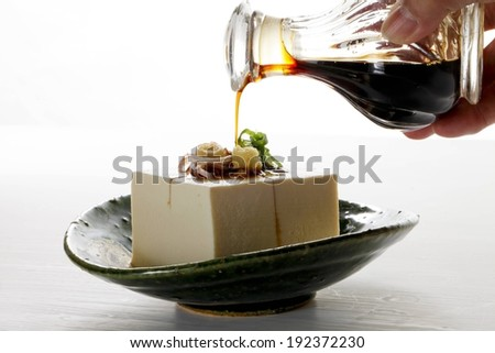 Someone drizzling sauce on a piece of food. - stock photo