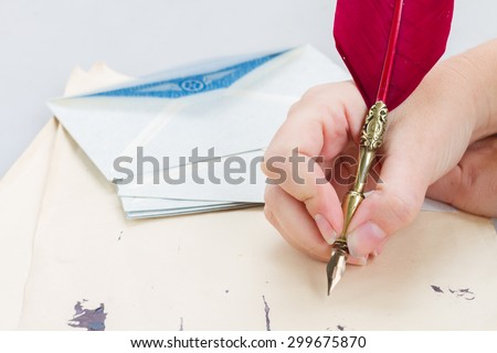 someone hand holding red feather pen  over old papers with ink blots - stock photo