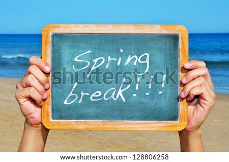 someone holding a blank blackboard at the beach with the sentence spring break written in it - stock photo