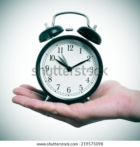 someone holding an alarm clock adjusting backward one hour at the end of the summer time - stock photo