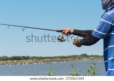 someone is fishing in the river - stock photo