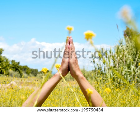 someone meditating with his hands in prayer mudra in a spring field - stock photo
