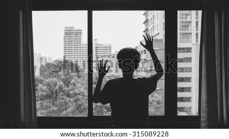 Someone standing by window with raindrops on a rainy day,Lonely silhouette in a window - stock photo