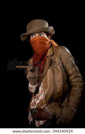 Someone wearing a hat, scarf on face, leather jacket and gloves with a cigar, a knife and a gun. - stock photo
