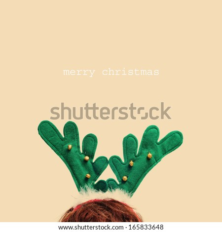 someone wearing a reindeer antlers headband and the sentence merry christmas in a beige background - stock photo