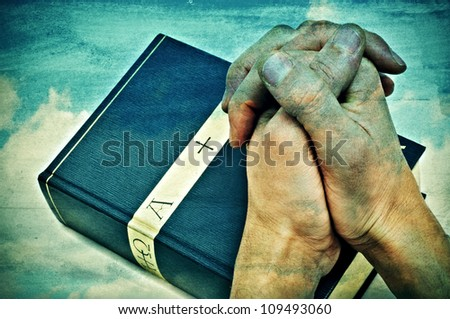 someone with hands clapsed praying on a bible - stock photo