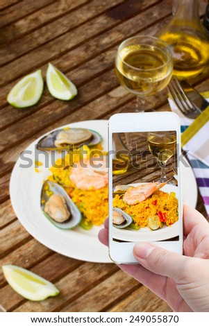 someones hand with mobile phone making  photo of paella - stock photo