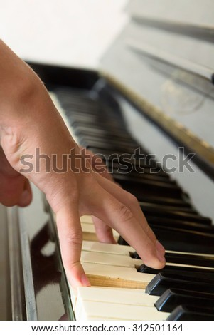 Someones hands playing music on piano keys - stock photo