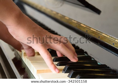 Someones two hands playing music on piano keys - stock photo