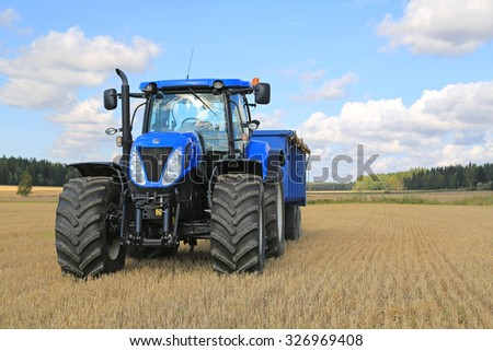 SOMERO, FINLAND - SEPTEMBER 12, 2015: New Holland T7.250 Tractor and blue agricultural trailer on stubble field. New Holland celebrates 12 decades of innovation in 2015. - stock photo