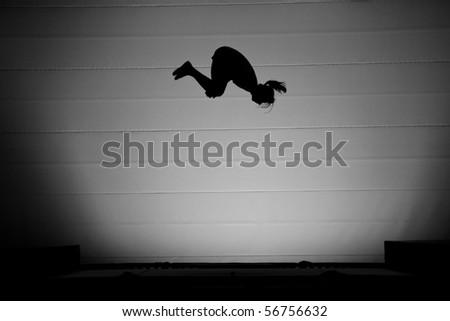 somersault silhouette on trampoline - stock photo