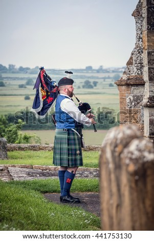SOMERSET, UK - JUNE 20, 2016: Bagpiper plays in churchyard overlooking countryside. - stock photo