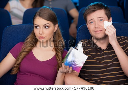 Sometimes he is too sentimental. Handsome young man holding handkerchief and crying while watching movie with his girlfriend at the cinema  - stock photo